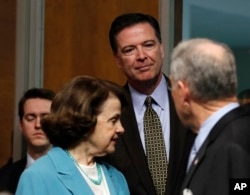 FILE - FBI Director James Comey, flanked by Senate Judiciary Committee Chairman Sen. Charles Grassley, R-Iowa, right, and the committee's ranking member Sen. Dianne Feinstein, D-Calif., arrives on Capitol Hill in Washington, May 3, 2017, to testify before the committee.