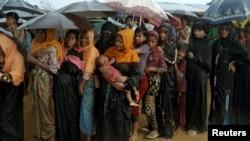 ជនភៀសខ្លួនរ៉ូហ៊ីងយ៉ាឈរតម្រង់ជួរក្នុងភ្លៀង ដើម្បីទទួលជំនួយមនុស្សធម៌ នៅជំរំ Kutupalong ក្នុងស្រុក Cox's Bazar ប្រទេសបង់ក្លាដេស កាលពីថ្ងៃទី១២ ខែតុលា ឆ្នាំ២០១៧។