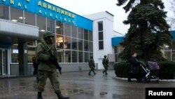Pria-pria bersenjata berpatroli di bandar udara di Simferopol, Krimea (28/2).