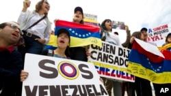 """Manifestan ki t ap pwoteste kont rejim Nicolàs Maduro a.... Enskripsyon ki sou youn nan pannkat yo (a goch) vle di """"Sekou pou Venezuela"""".."""