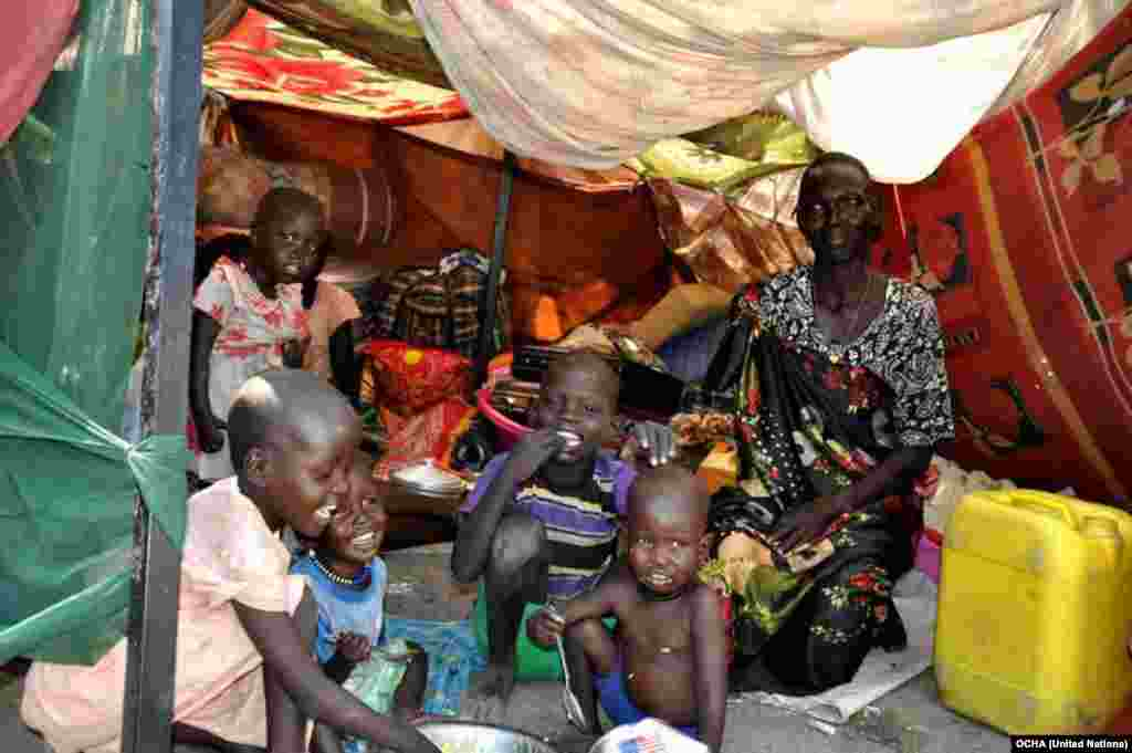 A woman and her children sit in their makeshift shelter at the U.N. compound in Malakal, where some 26,000 have sought shelter.