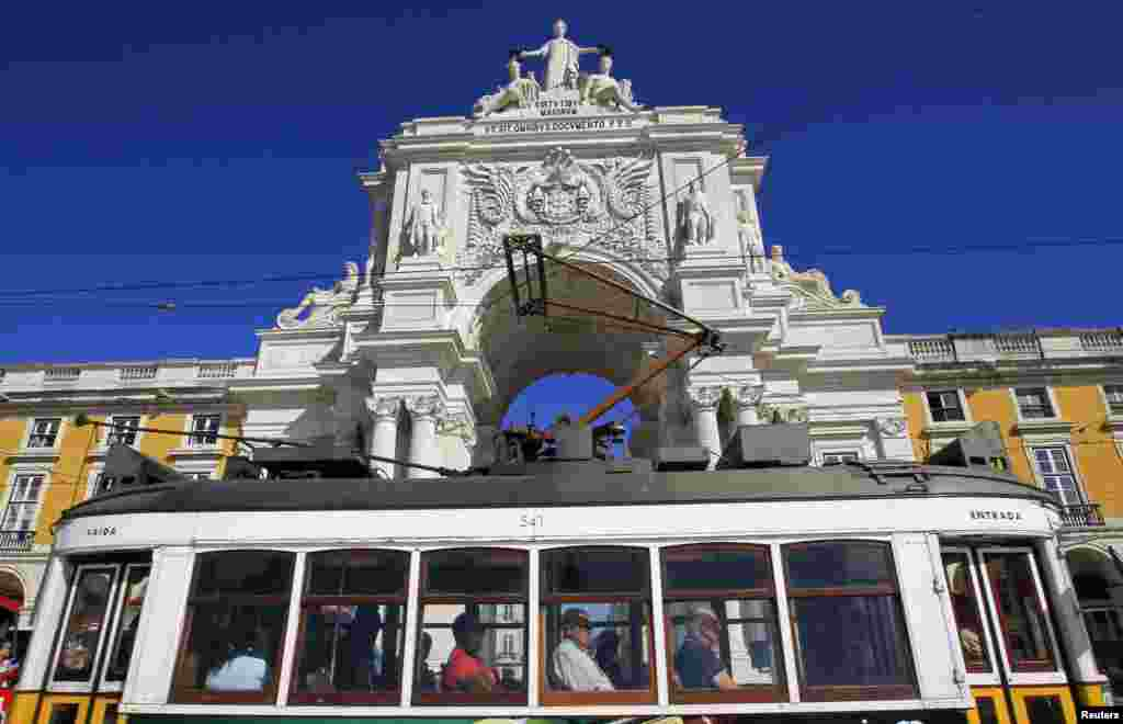 Passengers inside a tram pass in front of the main arch of Praca do Comercio square where the Finance Ministry is located, in Lisbon, Portugal.
