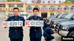 Officers of China's navy pose for photographs with the new (L) and old military car licence plates, in Qinhuangdao, Hebei province Apr. 28, 2013.