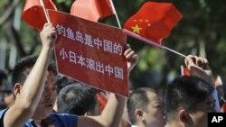 Para demonstran melambaikan bendera Tiongkok meneriakkan slogan=slogan anti Jepang dalam aksi protes di depan Kedutaan Jepang di Beijing.