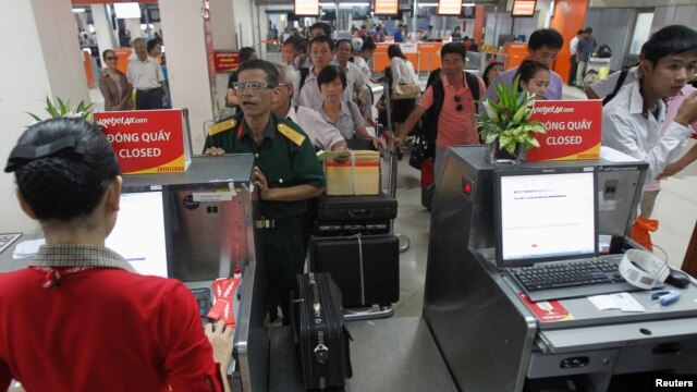 Hành khách xếp hàng tại quầy kiểm tra vé ở sân bay Tân Sơn Nhất, TP HCM.