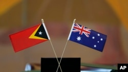 The flags of East Timor, left, and Australia are displayed during a ceremony at United Nations headquarters, Tuesday, March 6, 2018. Australia and East Timor signed a treaty that draws the first-ever maritime border between the neighbors.