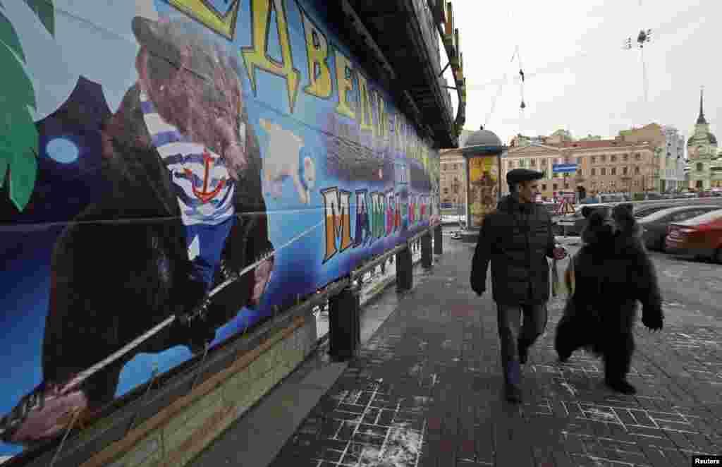 Ông Alexander Ivanov dẫn gấu Dasha 3 tuổi đi ngang qua quảng cáo đoàn xiếc lưu động của mình trên đường phố St. Petersburg của Nga.
