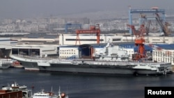 A general view shows navy soldiers standing on China's first aircraft carrier 'Liaoning' as it is berthed in a port in Dalian, northeast China's Liaoning province, September 25, 2012.