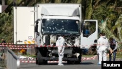 FILE - Investigators work near the heavy truck that ran into a crowd at high speed in Nice, France, July 15, 2016. A Maryland man allegedly inspired by that attack has been detained, the U.S. Justice Department said Monday.