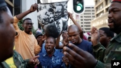 South Africa Protests: A supporter of the African National Congress, sings whilst holding a poster with the late party president Oliver Tambo's face outside the ruling party ANC headquarters in downtown Johannesburg, South Africa, Monday, Sept. 5, 2016.