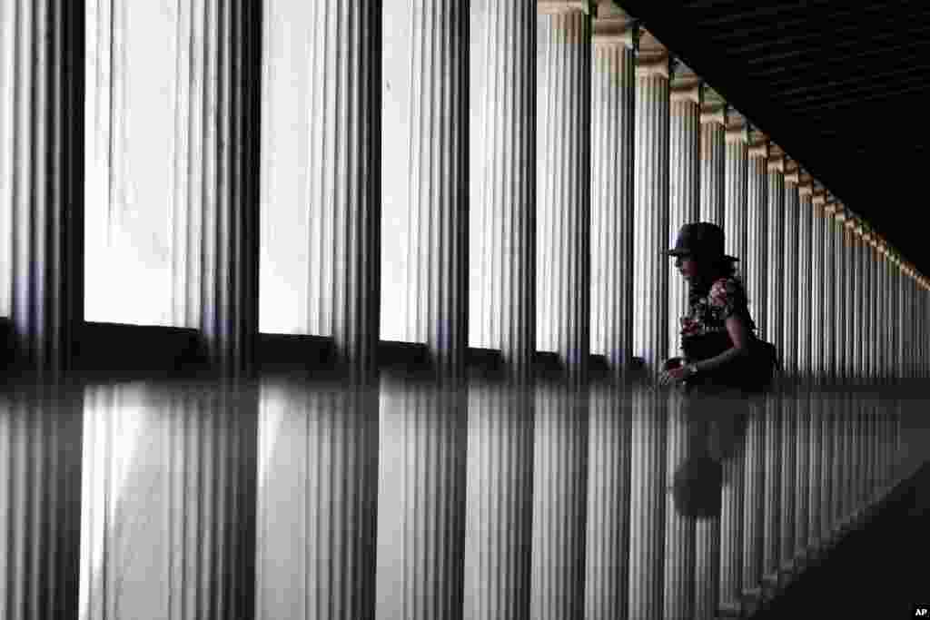 A tourist is reflected in a glass surface as she walks in the newly-opened first floor of the Museum of the ancient Agora, Stoa of Attalos, central Athens, Greece.