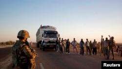 法国士兵2013年2月14日在马里加奥郊区的一个检查站搜索过路之人