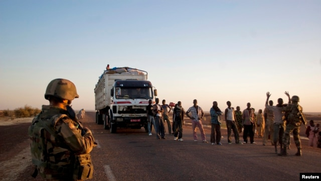 French soldiers search people at a checkpoint on the outskirts of Gao, Mali, February 14, 2013.