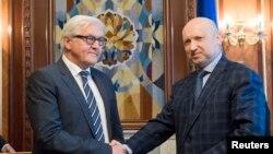 Presiden sementara Ukraina Oleksander Turchinov (kanan) berjabat tangan dengan Menlu Jerman Frank-Walter Steinmeier (kiri) dalam pertemuan di Kyiv (13/5).