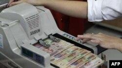 Trong 14 tháng qua, chính phủ Việt Nam đã phá giá tiền đồng 3 lần vì nguồn vốn nước ngoài không đủ để bù cho khoản nhập siêu