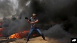 Palestinski demonstranti gađaju kamenicama izraelske vojnike za vreme sukoba na granici Gaze sa Izraelom.