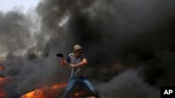 一名巴勒斯坦抗议者在加沙跟以色列的边界地带向以色列部队投掷石块(2018年4月20日)