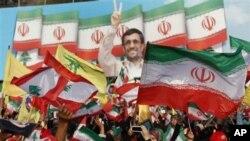 ພວກສະໜັບສະໜຸນການຕໍ່ສູ້ດ້ວຍກໍາລັງອາວຸດ ຂອງກຸ່ມຫົວຮຸນແຮງ Hezbollah ຕ້ານອິສະຣາແອລ ພາກັນ ໂບກທຸງເລບານອນ ແລະທຸງອີຣ່ານ ໃນຂະນະຟັງຄໍາປາໃສຂອງປະທານາທິບໍດີອີຣ່ານ ທ່ານ Mahmoud Ahmadinejad ຢູ່ບ່ອນໂຮມຊຸມນຸມ ທີ່ຈັດຂຶ້ນໂດຍກຸ່ມ Hezbollah ໃນພາກໃຕ້ເລບານອນ ໃກ້ໆຊາຍແດນ ອິສະຣາແອ
