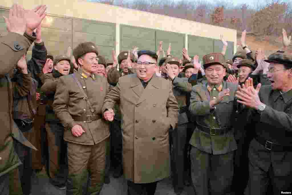 북한 김정은 국무위원장이 18일 서해위성발사장에서 신형 고출력 로켓엔진 지상분출실험을 참관한 뒤 관계자들과 함께 환호하고 있다.