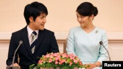 Princess Mako, the elder daughter of Prince Akishino and Princess Kiko, and her fiancee Kei Komuro, a university friend of Princess Mako, smile during a press conference to announce their engagement at Akasaka East Residence in Tokyo, Japan, Sept. 3, 2017.