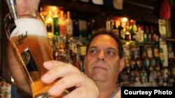 FILE - The Guildhall Bar's present owner, Fernando Coimbra, a South African of Portuguese descent, pours another pint of beer in the historical venue. Photo by Darren Taylor