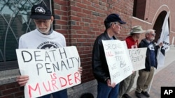 """FILE- A group from """"Veterans for Peace"""" picket outside the Moakley Federal Courthouse as inside jury deliberations continue in the penalty phase of the trial of Boston Marathon bomber Dzhokhar Tsarnaev, May 15, 2015."""
