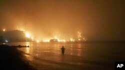 Seorang pria menyaksikan kebakaran hutan mendekati pantai Kochyli dekat desa Limni di pulau Evia, sekitar 160 kilometer utara Athena, Yunani, Jumat, 6 Agustus 2021. (AP Photo/Thodoris Nikolaou)