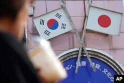 FILE - A woman walks past an advertisement featuring Japanese and South Korean flags at a shop in the Shin Okubo area in Tokyo, Aug. 2, 2019.