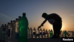 A boy is silhouetted against the setting sun while arranging bottles of drinking water for sale along Karachi's Clifton beach.