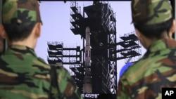 Soldados surcoreanos observan el cohete norcoreano en las noticias.