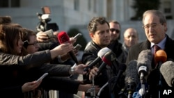 Journalists reach out to ask questions to Syrian Deputy Foreign Minister Faisal Makdad, right, during a short briefing to journalists after a meeting with the Syrian government at the United Nations headquarters in Geneva, Switzerland, Tuesday, Jan. 28, 2