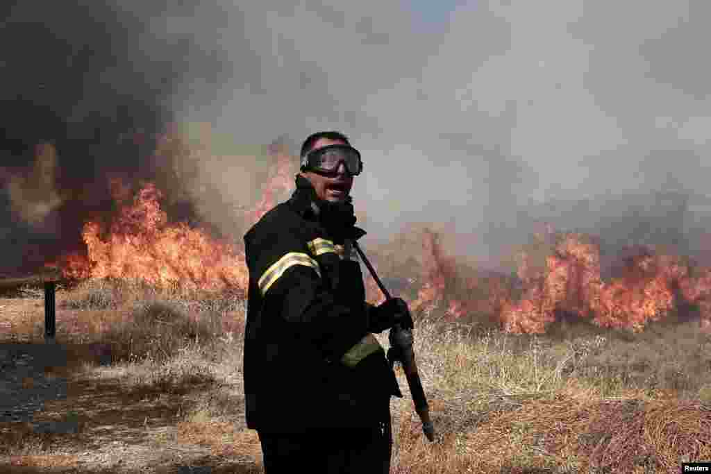 A firefighter shouts at a colleague as he tries to extinguish a bushfire at Markopoulo region a few miles southwest of Athens, Greece.