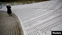 FILE - Fadila Efendic prays near memorial plaques at the Potocari genocide memorial center near Srebrenica, March 18, 2015.