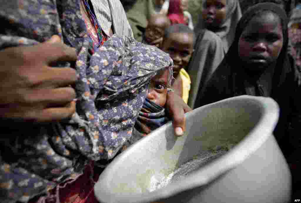 July 19: A woman carrying her baby queues for food in a camp established by the Somali Transitional Federal Government for the internally displaced people in Mogadishu. The United Nations said on Wednesday two regions of southern Somalia had been hit by t