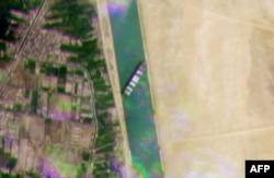 Une image satellite publiée par Planet Labs Inc le 24 mars 2021 montre le porte-conteneurs MV 'Ever Given' (Evergreen) appartenant à Taiwan, un navire de 400 mètres de long et 59 mètres de large, logé sur le côté et gênant tout trafic sur la voie navigabl