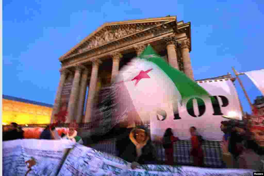 15일 프랑스 파리의 신전 앞에서 시리아 폭력 사태를 비난하며 시리아 국기를 펄럭이는 시위대.