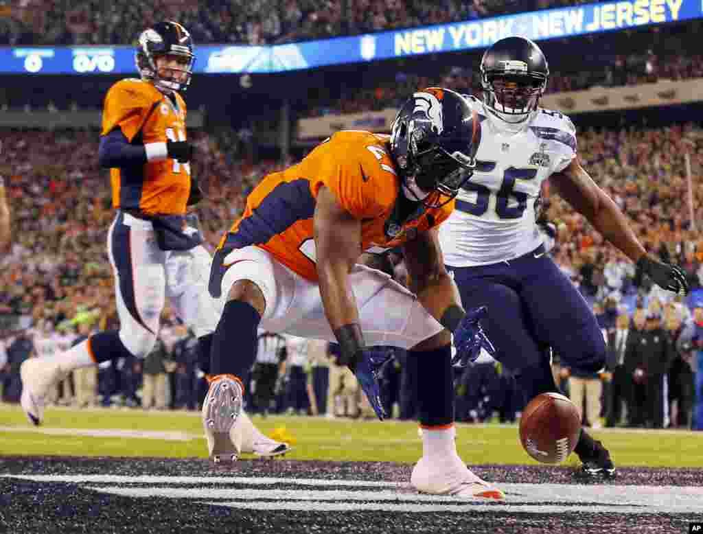 Denver Broncos' Knowshon Moreno reaches for a loose ball after the snap passed teammate Peyton Manning, left, during the first half of the NFL Super Bowl XLVIII football game, Feb. 2, 2014, in East Rutherford, N.J.