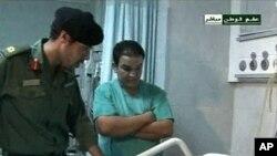利比亚国家电视台8月9日截屏显示卡扎菲的儿子哈米斯的人正在看望医院里受伤的人