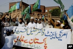 "Supporters of Pakistani religious party Jamaat-e-Islami rally holding a banner reads ""Release of American agent doctor Shakil Afridi is betrayal from Pakistan,"" in Peshawar, Pakistan, Friday, Aug. 30, 2013."