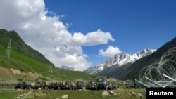 Indian army soldiers walk past their parked trucks at a makeshift transit camp before heading to Ladakh, near Baltal, southeast of Srinagar, June 16, 2020.