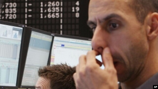 Traders watch their screens at the stock market in Frankfurt, Germany, Monday, Sept.12, 2011, when the German stock index DAX went down under 5000 points.