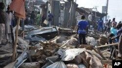 Warga memeriksa lokasi ledakan di Maiduguri, Nigeria, Selasa (1/7).
