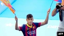 Le Brésilien Neymar da Silva Santos Junior, nouveau joueur du FC Barcelone, brandit deux drapeaux de son nouveau club lors de sa présentation au stade Camp Nou à Barcelone, le 3 juin 2013.
