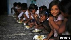 Các em học sinh Ấn Ðộ ăn bữa trưa miễn phí tại một trường tiểu học do chính phủ điều hành trong làng Brahimpur, phía đông bang Bihar, ngày 19/7/2013.
