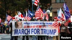 Supporters of U.S. President Donald Trump hold a banner as they march ahead of the inauguration of President-elect Joe Biden, amid the coronavirus disease (COVID-19) outbreak, at Ginza district in Tokyo, Japan January 20, 2021. REUTERS/Issei Kato