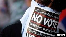 """Seorang demonstran anti-pemerintah Thailand mengenakan masker bertuliskan """"No Vote"""" saat melakukan pawai protes di Bangkok (31/1)."""