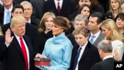 Donald Trump is sworn in as the 45th president of the United States by Chief Justice John Roberts as Melania Trump looks on during the 58th Presidential Inauguration at the U.S. Capitol in Washington, Jan. 20, 2017.