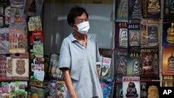 Un homme portant un masque facial pour aider à freiner la propagation du nouveau coronavirus se tient devant une librairie à Bangkok, en Thaïlande, le mardi 26 mai 2020. (AP Photo/Sakchai Lalit)