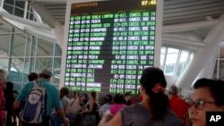 Hành khách đang xem danh sách các chuyến bay bị hủy bỏ tại phi trường quốc tế Ngurah Rai ở Bali, Indonesia ngày 27/11/2017..