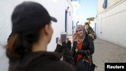 Falconer Maroua (à gauche) photographie une femme qui pose avec un faucon sur son épaule à Sidi Bou Said, une destination touristique populaire à proximité de Tunis, 2 février 2016.